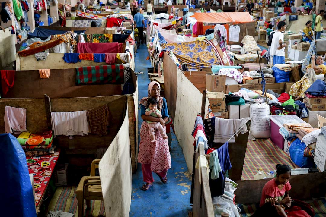 2017年10月17日,菲律賓南部城市馬拉維,因軍隊五個多月前要剿滅市內與「伊斯蘭國」恐怖組織有聯繫的恐怖份子成員,數百名當地居民被撤離家園,至今仍然住在當地多功能場館改建的臨時居所裡,一名婦女抱著孩子在場館內走過。