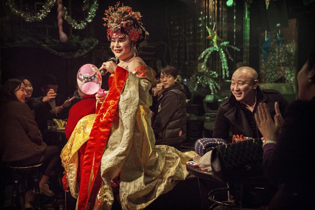 一名穿著中國特色衣飾的變裝皇后在酒吧內表演。