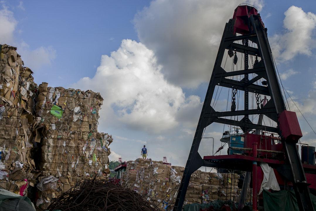 青衣醉酒灣起卸區,工人將廢紙卸到貨船上,準備運往中國內地。