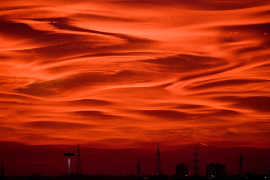 2017年10月29日,意大利城市米蘭的黃昏時分,電塔和建築物的剪影撞在泛紅的天空上。