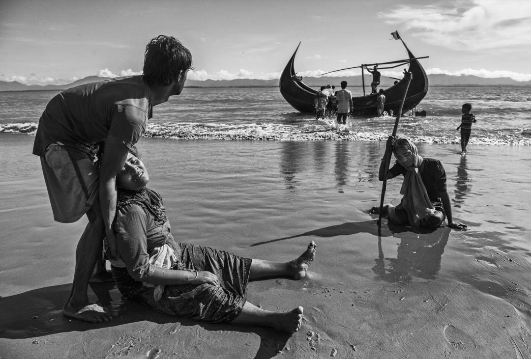 2017年10月1日,在越過緬孟邊境的納夫河後,一名筋歇力疲的羅興亞婦人倒臥在科克斯巴扎爾縣的沙灘上。