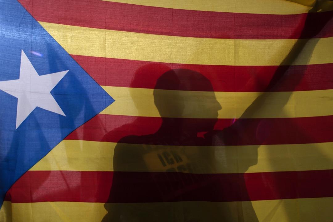 2017年10月1日,西班牙加泰隆尼亞地區城市格拉納達,一名男子在參與支持獨立的遊行期間拿著加泰隆尼亞旗。