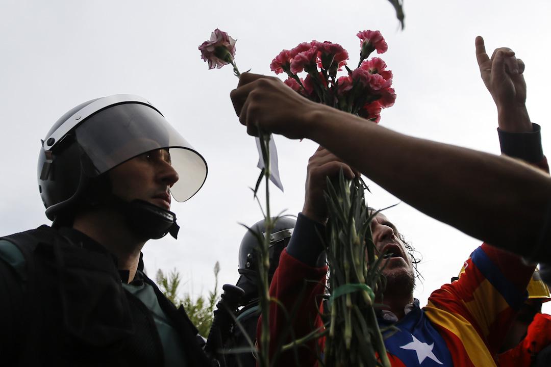 2017年10月1日,警察阻止公投市民進入加泰羅尼亞自治區獨立公投票站,雙方對峙,一位市民向警察送上鮮花。