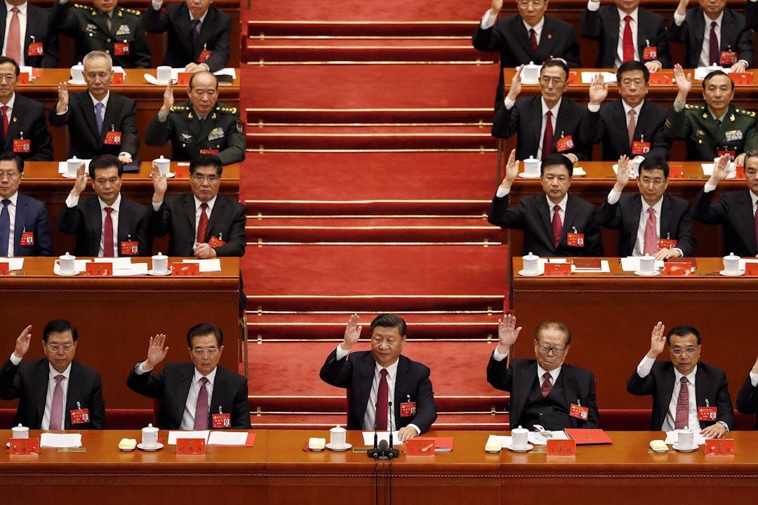 2017年10月24日,習近平在十九大閉幕儀式上,與前國家領導人及共產黨委員一同舉手通過工作報告。