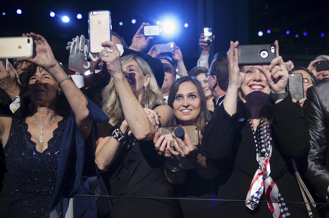 2017年1月20日,特朗普支持者觀看美國總統特朗普和第一夫人梅拉尼婭跳舞。 攝:Brendan Smialowski / AFP