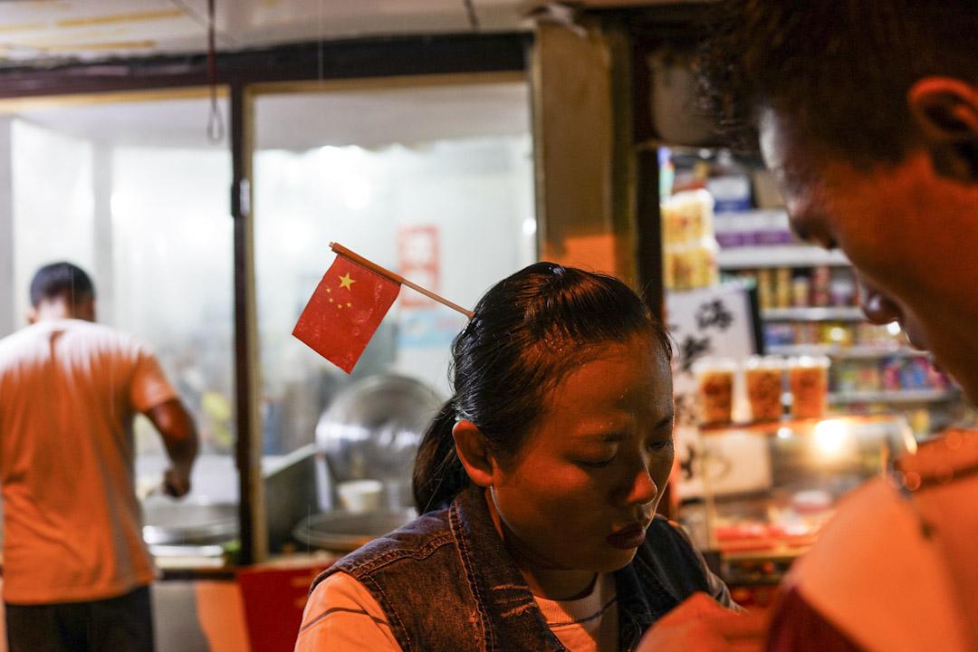 2017年10月1日,上海一名女士在她的頭髮上戴上了一面國旗,以慶祝國慶。 攝:Chandan Khanna /AFP/Getty Images