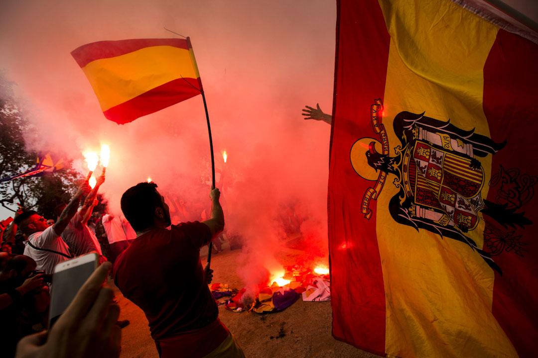 2017年10月12日,西班牙城市巴塞隆那,極端右翼示威者一邊揮舞著代表支持西班牙憲法的西班牙國旗,一邊焚燒代表加泰隆尼亞獨立的獨立旗。