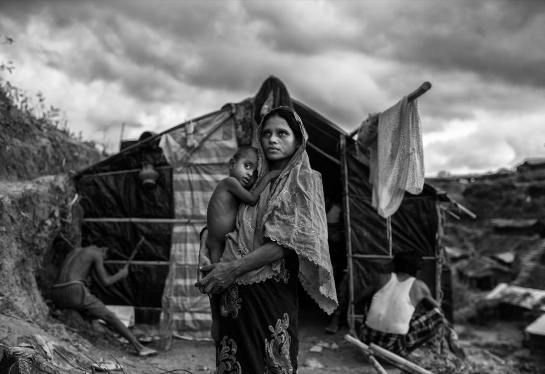 2017年9月27日,一名羅興亞婦人站在科克斯巴扎爾縣的難民營裡抱著孩子。