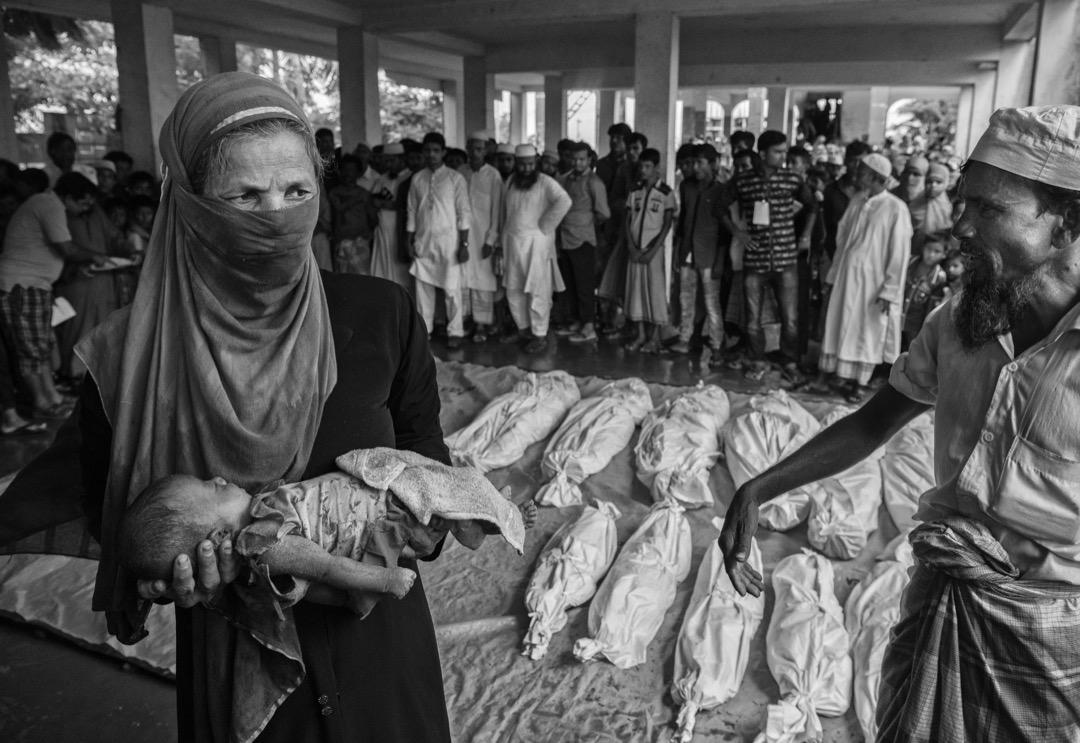 2017年9月29日,一名羅興亞婦人抱著一名男嬰的遺體。一艘從緬甸開往孟加拉,載著羅興亞難民的船在越過緬孟邊境的納夫河時翻沉,她身後用白布包裹著的都是沉船事件中的死者。