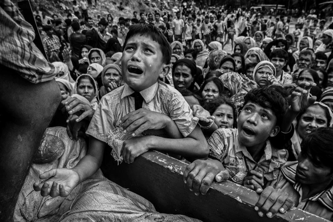 2017年9月20日,一輛為當地非政府組織運送救援物資的貨車抵達孟加拉科克斯巴扎爾縣的一個難民營,一名羅興亞難民男孩哭著攀上貨車拿物資。 攝:Kevin Frayer/Getty Images