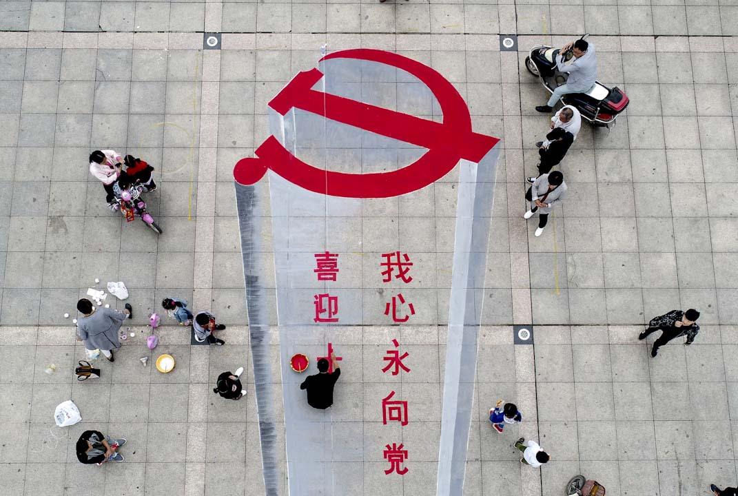 2017年10月6日,一名男子在河南的一幅地上繪畫中國共產黨的黨徽,以迎接10月18日中共十九大的來臨。