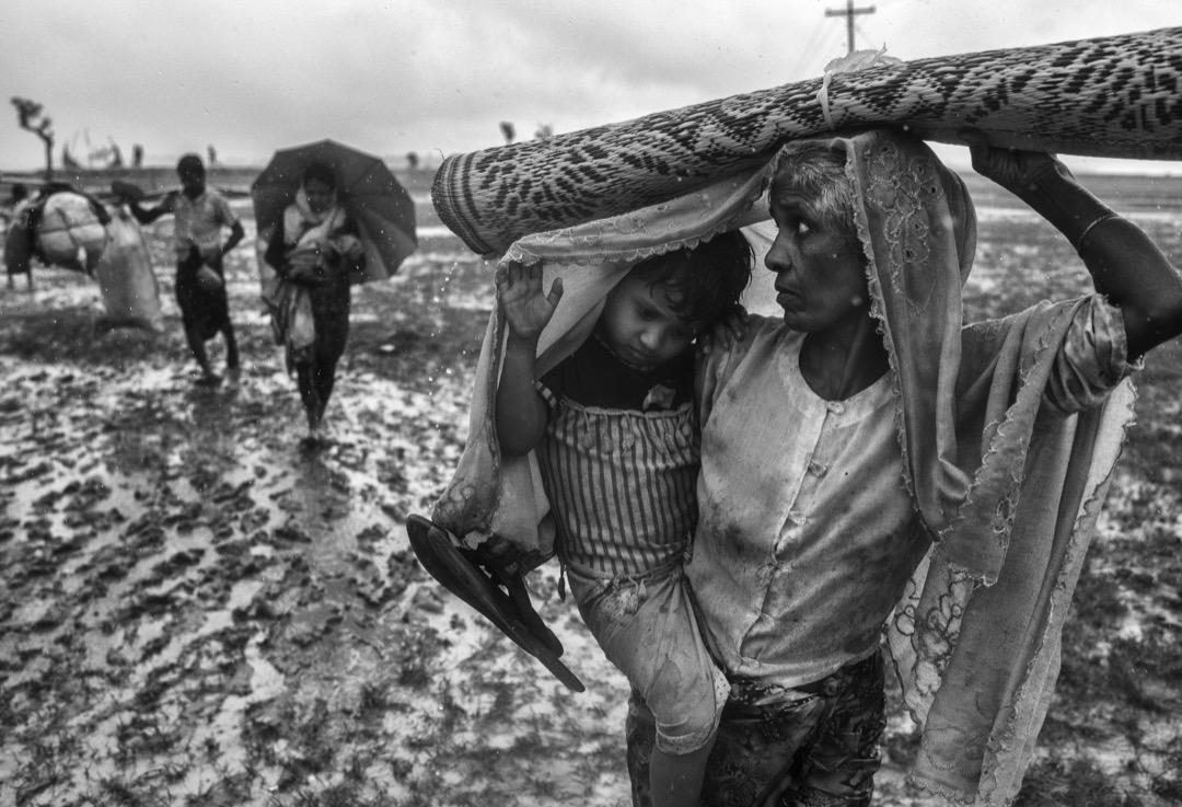 2017年9月28日,一名羅興亞難民婦人抱著孩子從納夫河徒步到臨時難民營。