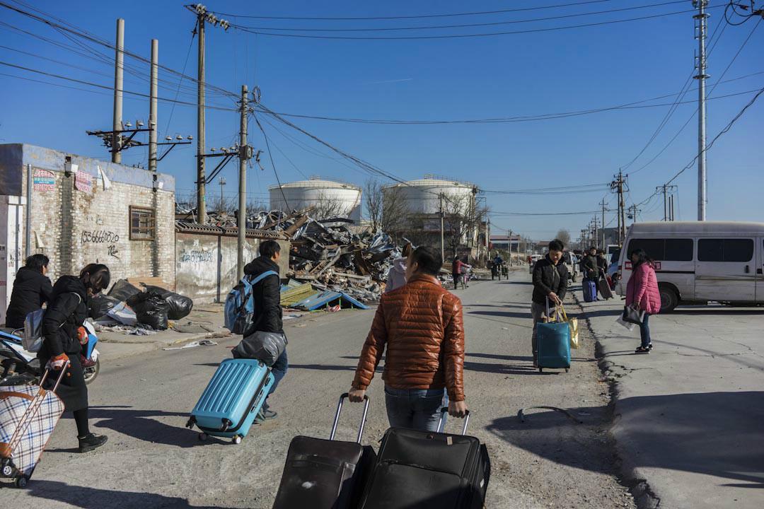 2017年11月26日上午,一群來自湖北的外來租戶拖着行李箱離開新建村。 攝:Bernard/端傳媒