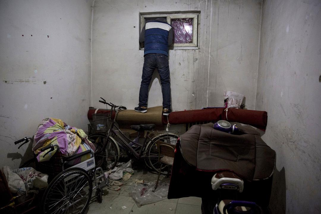 2017年11月27日,一名男子在北京郊區公寓的窗戶向外看,房子已近清空。自大興火災發生後,北京政府立即部署安全隱患大整治專項行動,目的就是為了人民生命的安全,一週之內,可能有多達二十萬「外地來京低端人口」被暴力驅離,淪為北京難民。 攝:Ng Han Guan / AP