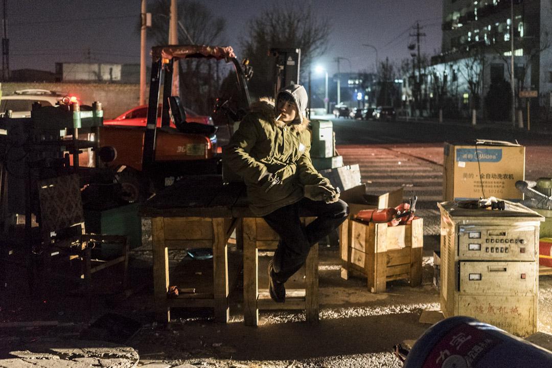 2017年11月25日晚上,新建村村口,一家洗車場即將搬遷到重慶,工作人員在看守設備,等待夜間裝車。北京當天發布大風預警,最高陣風可達6-7級。 攝:Bernard/ 端傳媒