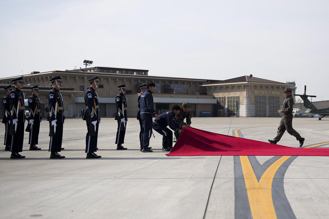 2017年11月7日,南韓儀仗隊正在跑道上整理紅地氈,預備迎接美國總統特朗普乘坐的空軍一號降落。