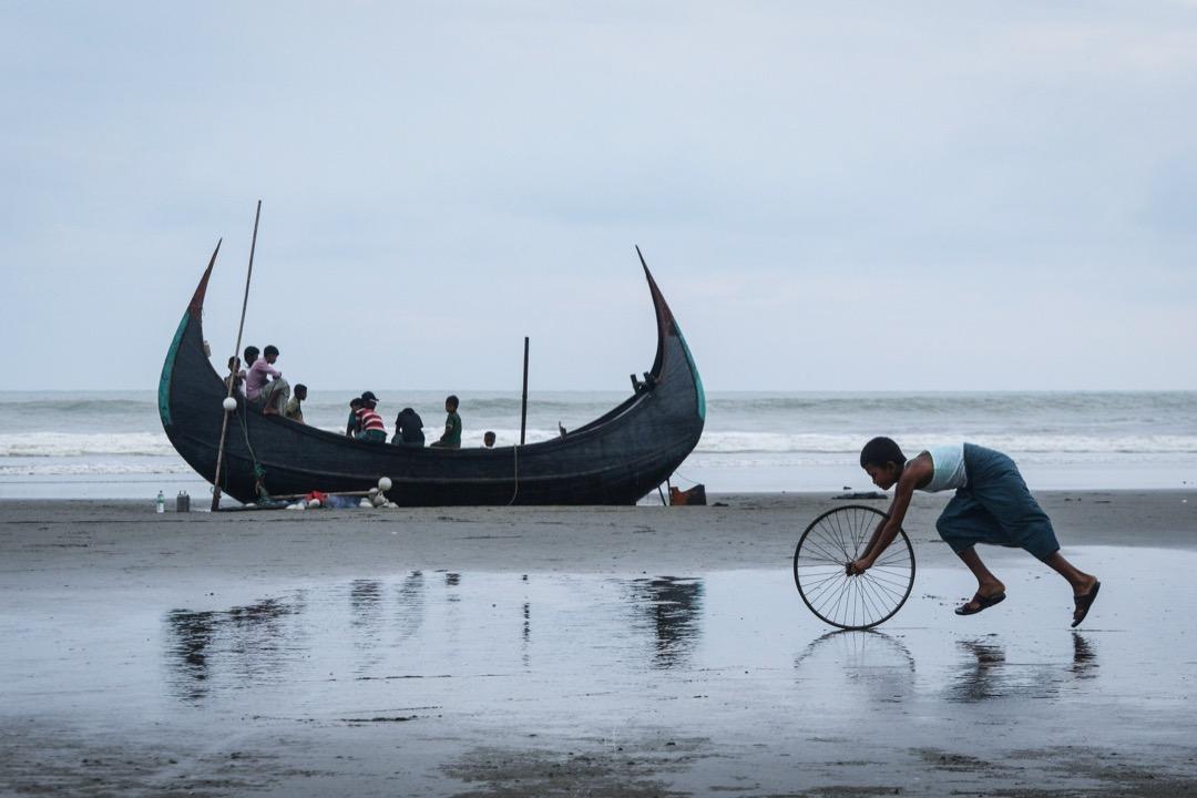 2017年10月31日,孟加拉科克斯巴扎爾縣,一名孟加拉男孩在納夫河畔的沙灘上玩沙,他身後載著羅興亞難民的船隻剛在河上發生致命意外。