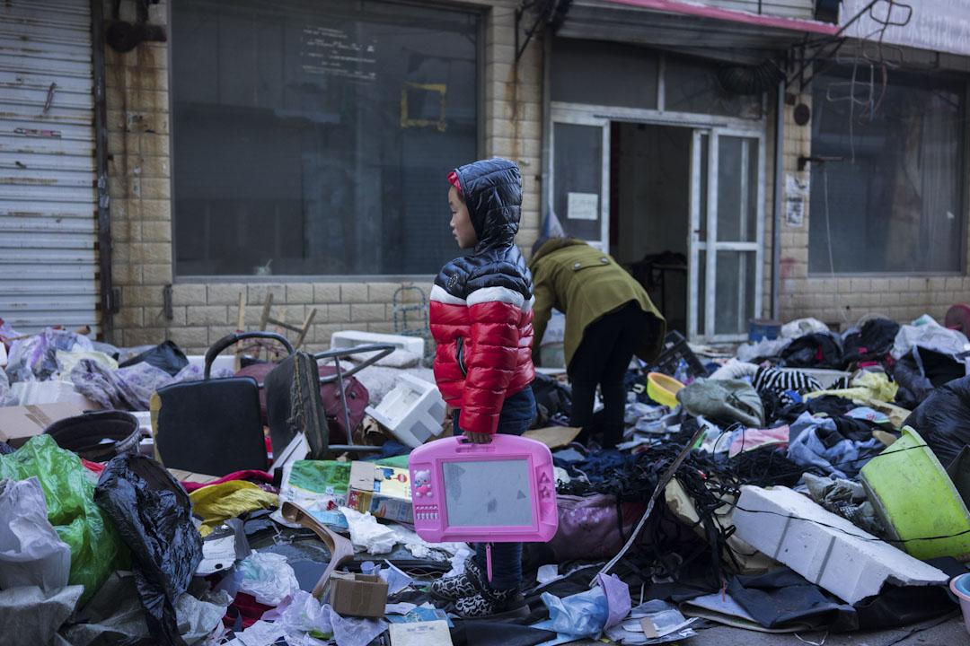 2017年11月26日下午,新建村街道上一個小孩和家人在堆滿廢棄物的街道上尋找能用的物品。