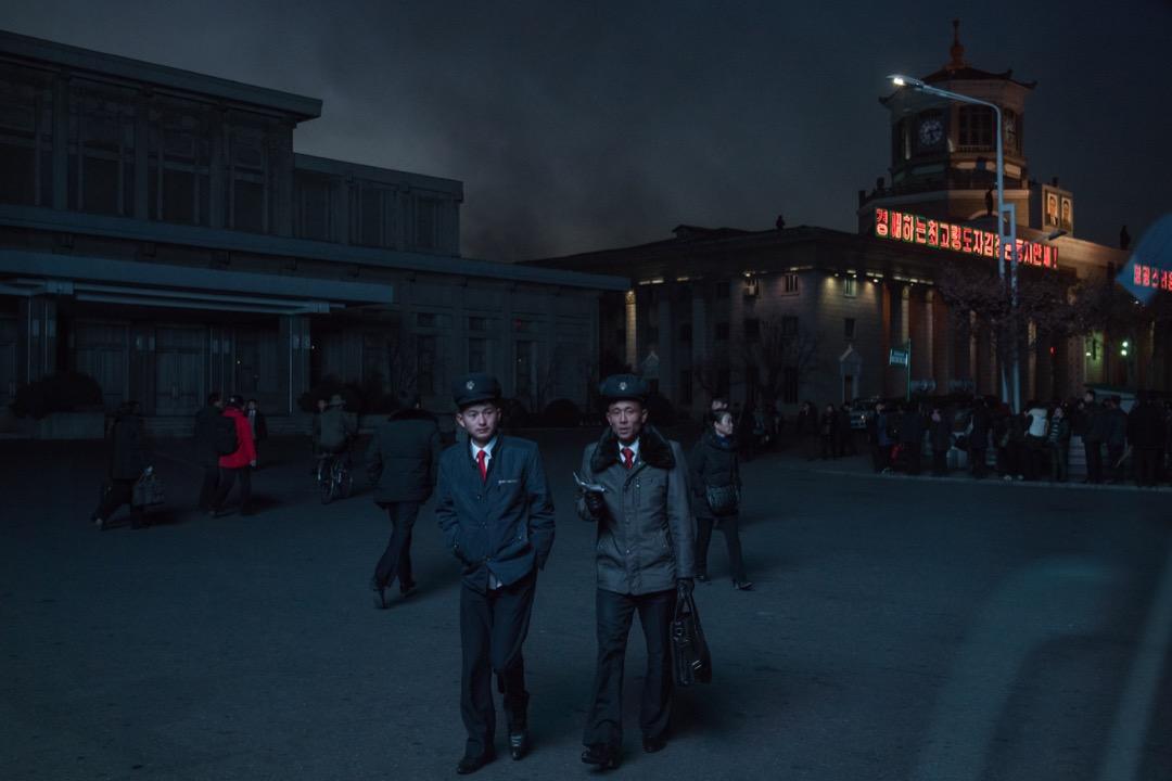 2017年11月16日,北韓首都平壤,兩名學生行經中央火車站外的大型屏幕。
