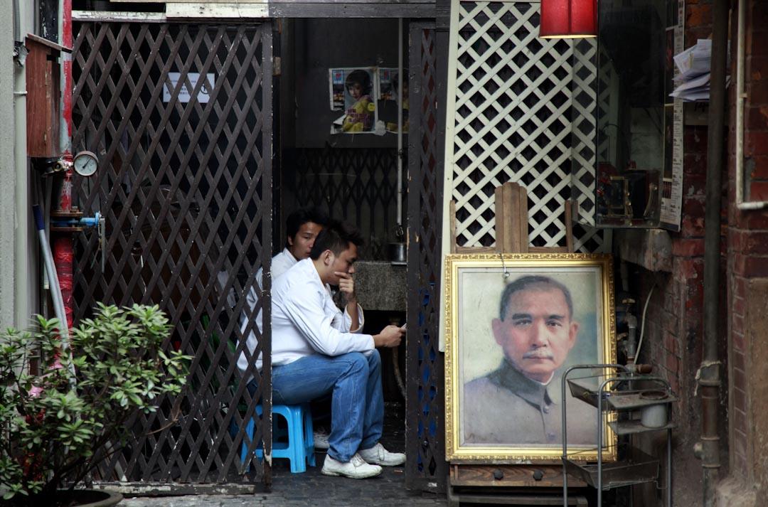 2011年11月9日,上海一間餐廳的員工在孫中山的肖像旁休息。
