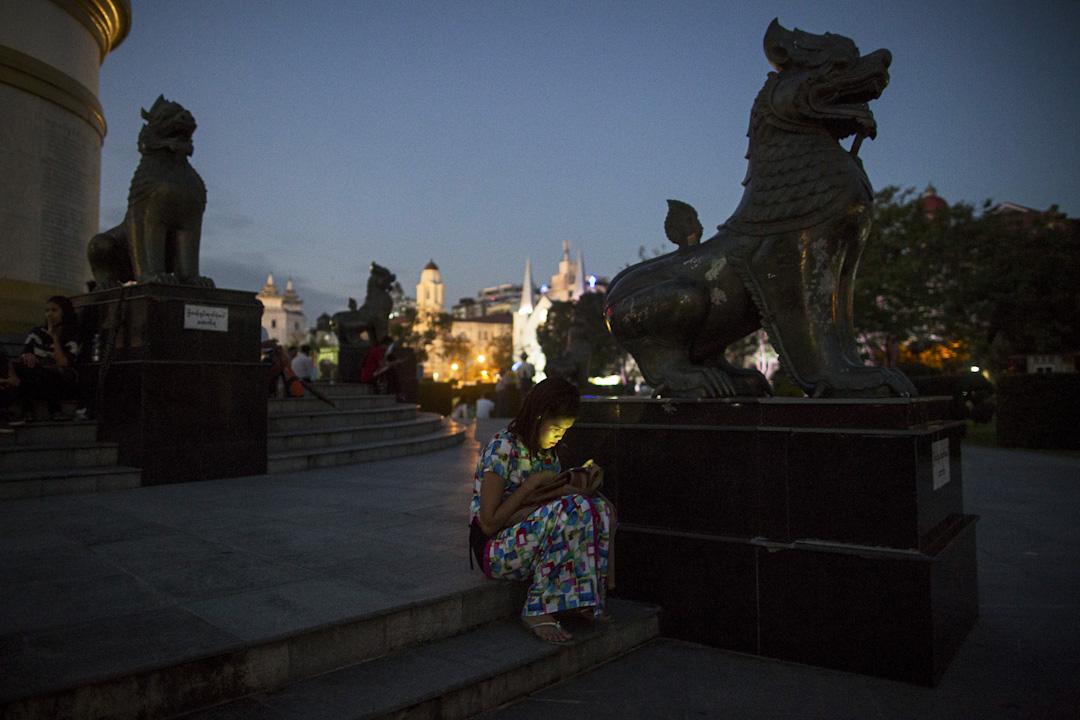 2015年10月14日,緬甸仰光夜間,一名婦女坐在瑪哈班都拉花園獨立紀念碑旁邊的一座雕像旁邊,樣子被手機屏幕照亮。 攝:Brent Lewin/Bloomberg via Getty Images