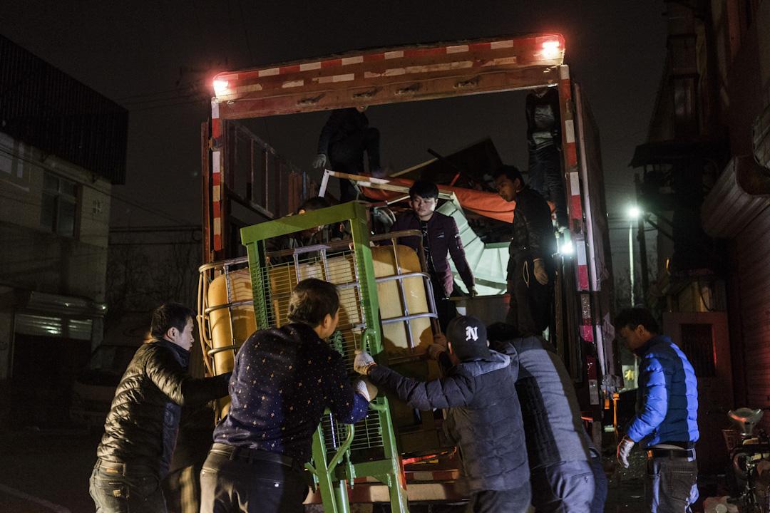 2017年11月25日晚上,服裝廠的搬運現場。服裝廠老闆說北京周邊的地租在這兩天猛漲,但她必須得租個地方開工,否則工人都將失業。 攝:Bernard/ 端傳媒