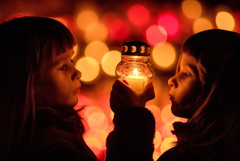 2017年11月1日,斯洛伐克一對五歲的孿生姐妹Amalia和Lesana,在萬聖節的晚上在墓地玩蠟燭。 攝:Joe Klamar /AFP/Getty Images