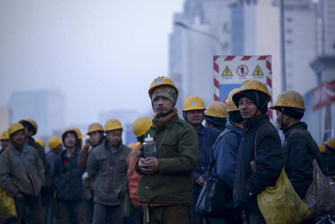 一個有良知的社會,都不會容忍對人的如此不尊重;一個社會主義社會,更不會容忍對工人、對勞動本身的不尊重。圖為一批中國工人在北京的一個建築工地外等候穿梭巴士。 攝:Wang Zhao /AFP/Getty Images
