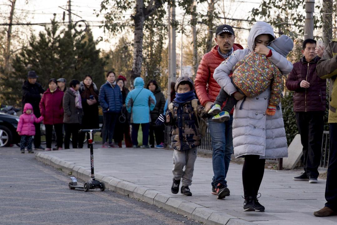 2017年11月24日,北京紅黃藍幼兒園幼兒虐童事件曝光後,一名家長帶著孩子辦理了退學。 攝:Imagine China