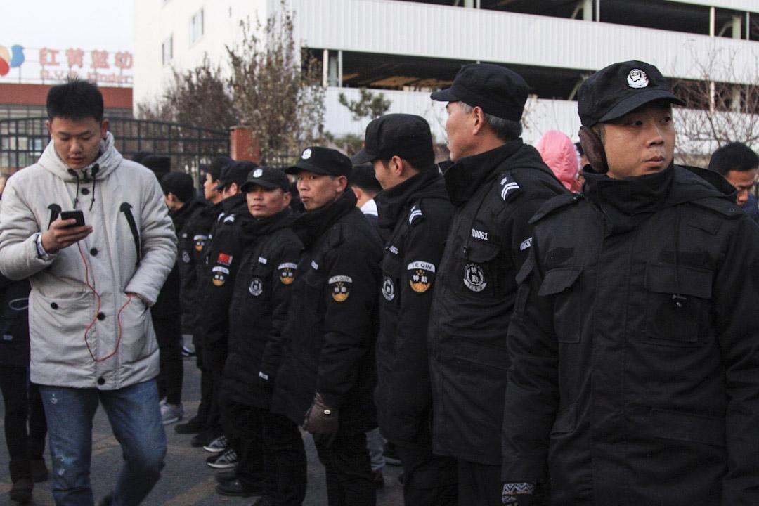 2017年11月23日,北京紅黃藍幼兒園門外聚集了許多來接孩子放學的家長,現場特勤人員排成人牆維持秩序。