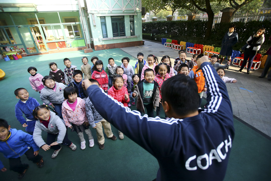 幼兒園一名老師正在和學童們一起在操場上課玩耍,眾家長在旁觀看。 攝:上海青年報 /Imagine China