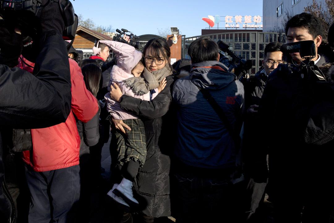 2017年11月24日早上,因媒體曝出體曝出及多名北京幼兒家長反映,北京紅黃藍幼兒園幼兒被老師用針紮、餵食成分不明的白色藥片,當天幼兒園門口聚集了很多家長和記者,一名家長抱著孩子走出學校,告訴媒體已經帶著孩子退學。  攝:Imagine China