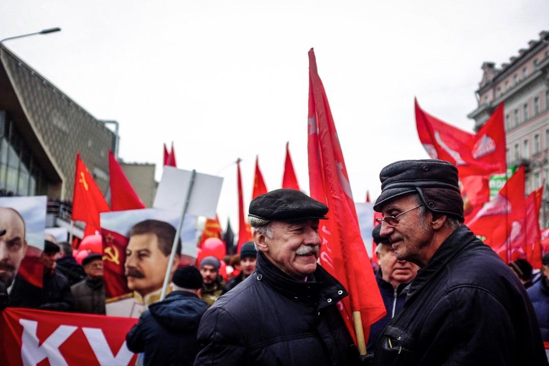 2017年11月7日,俄羅斯首都莫斯科,兩名參與十月革命百週年紀念遊行的老人在領袖像下等候遊行隊伍出發。