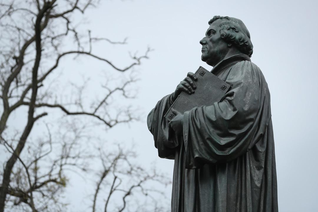 500年前,年僅33歲的年輕神學教授馬丁路德,在贖罪券議題上,不認同時任教宗,因此把一紙《九十五條論綱》釘在諸聖堂門上,藉此抗議。圖為位於德國城鎮艾森納赫 (Eisenach) 的馬丁路德像。 攝:Sean Gallup/Getty Images