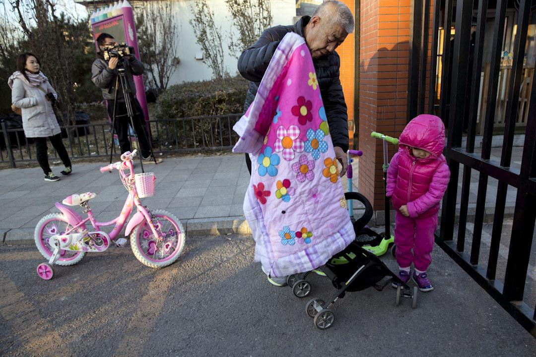 2017年11月24日,北京紅黃藍新天地幼兒園,家長於放學後接孩子回家。 攝:Ng Han Guan / AP