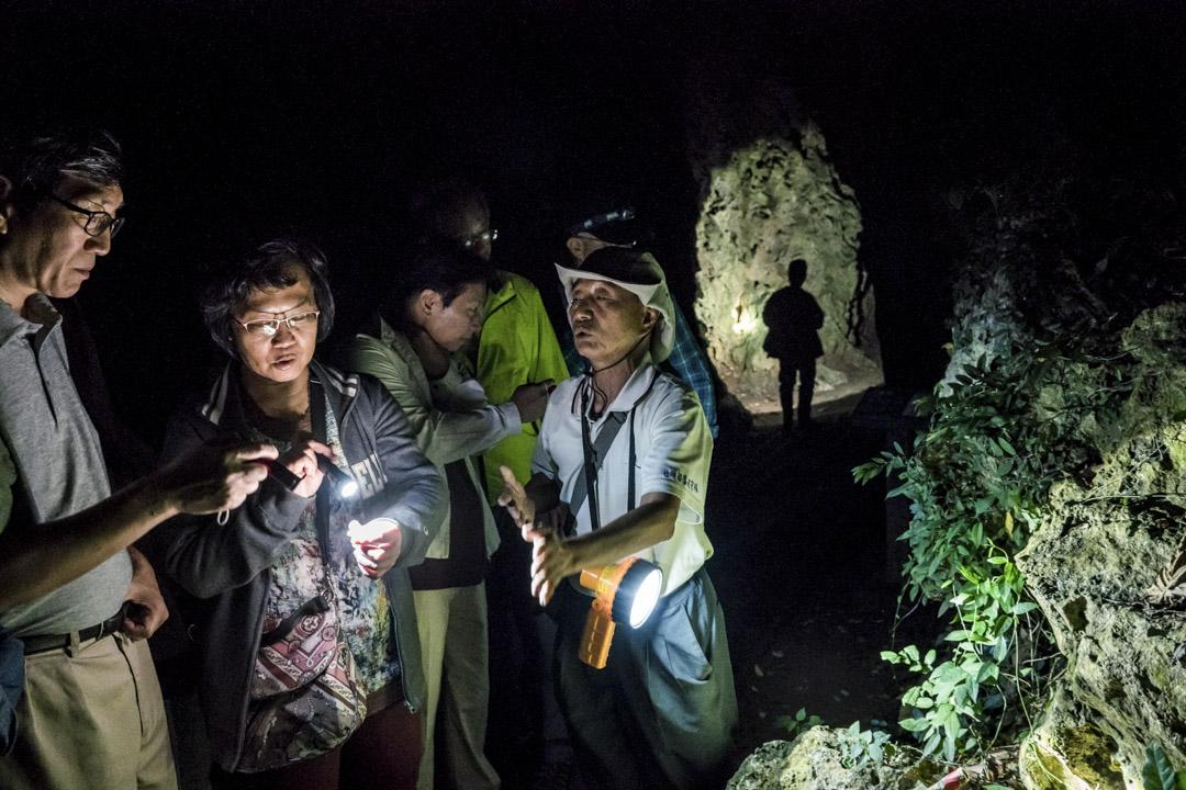 左拿手電筒、右拿登山杖,年已七十的社頂部落居民蔡正榮帶領導覽團參觀五色鳥的樹洞。過去十二年,二十五個導覽員,在這裡創造台灣第一個生態旅遊社區。 攝:王文彥/端傳媒
