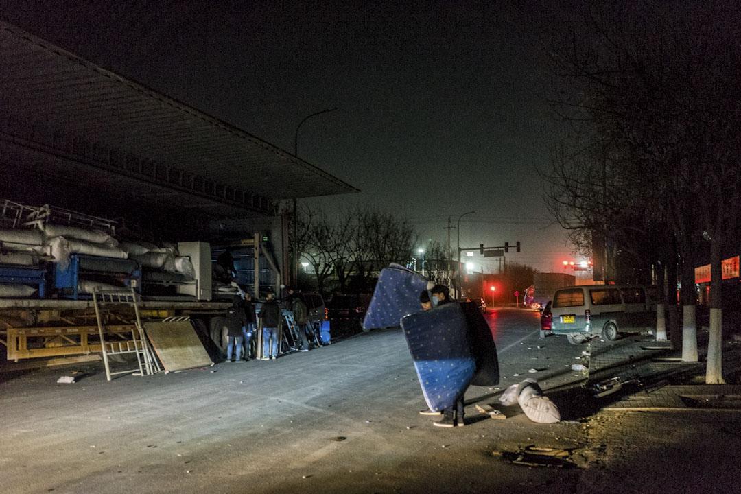 2017年11月25日晚上,工人將床墊搬到馬路對面的卡車上,之後他們將到遠離北京的新廠區安置。