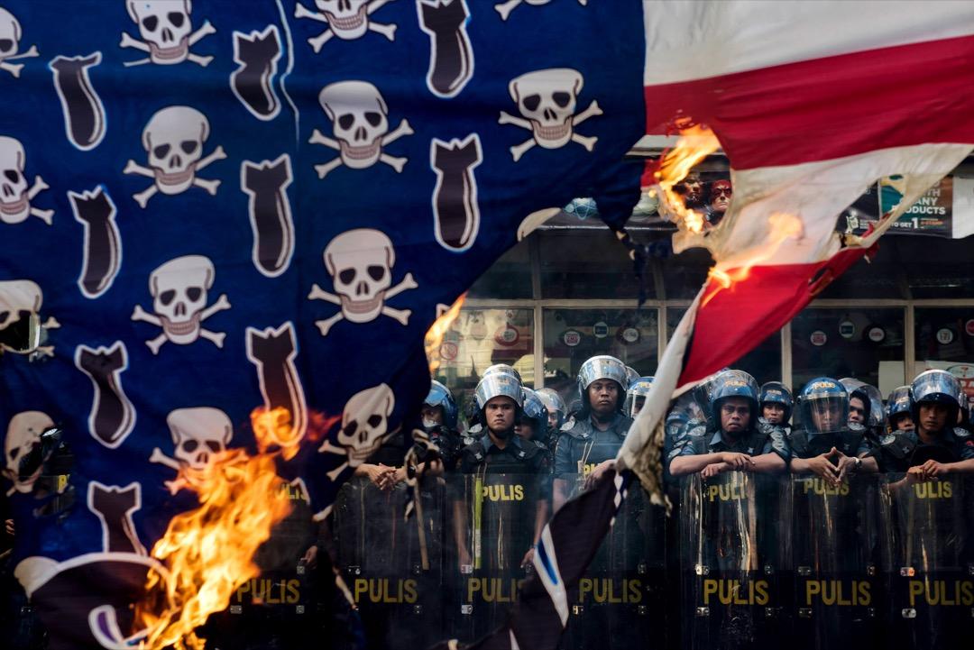 2017年11月12日,菲律賓首都馬尼拉,數百名示威者到街頭燃燒美國國旗抗議美國總統特朗普到訪,防暴警察戒備。