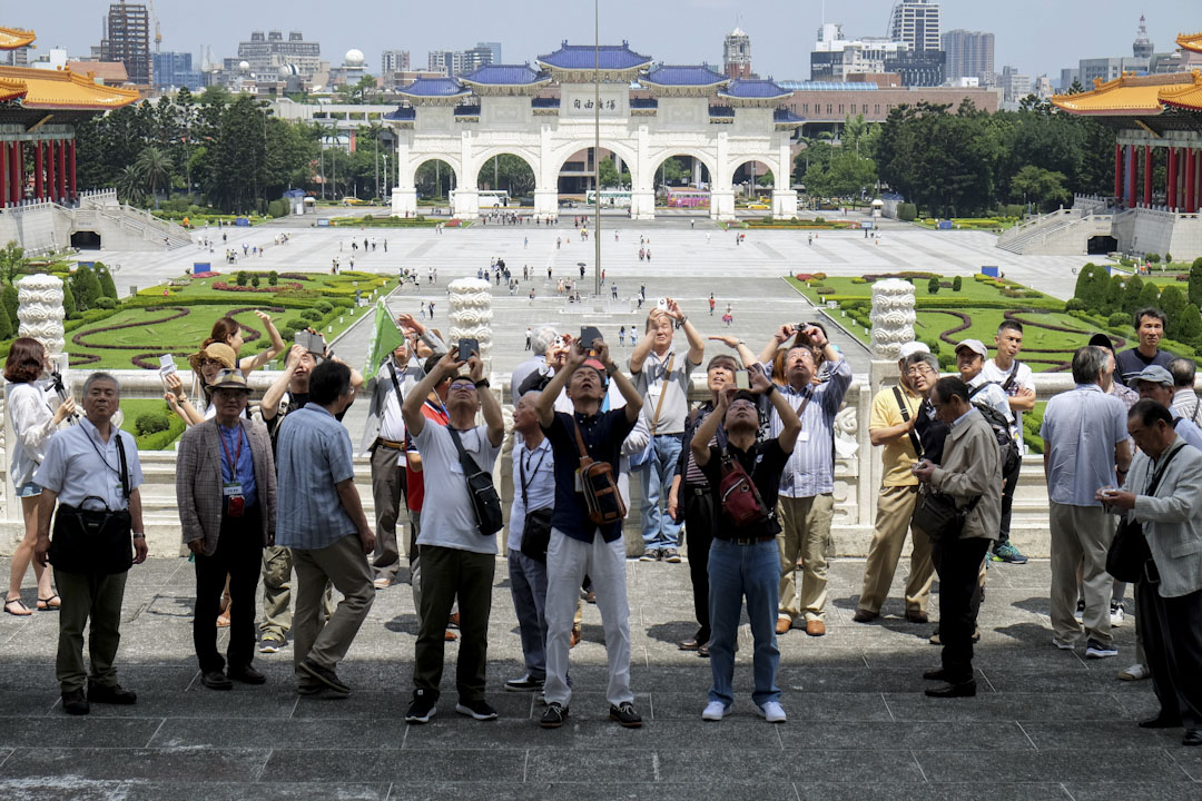 自2008年馬英九總統後開放中國大陸居民赴台灣旅遊,從強制跟團到漸漸依城市發達程度開放個人自由行,每日赴台限制人數也逐漸放寬。從2008年的32.9萬人次逐年增加,2015年來到418萬人次的最高峰。圖為遊客在台北的自由廣場拍照。 攝:Sam Yeh /AFP/Getty Images