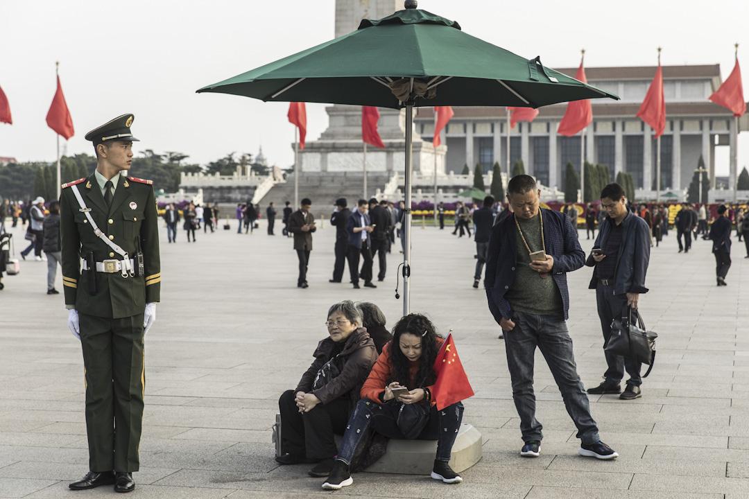 在人工智能和大數據時代,中國當局在網絡空間和實體空間的監控手段日益更新:互聯網上的敏感詞庫隨着社會熱點事件不斷擴充。圖為北京天安門廣場,市民正在使用智能手機。 攝:Qilai Shen/Bloomberg via Getty Images