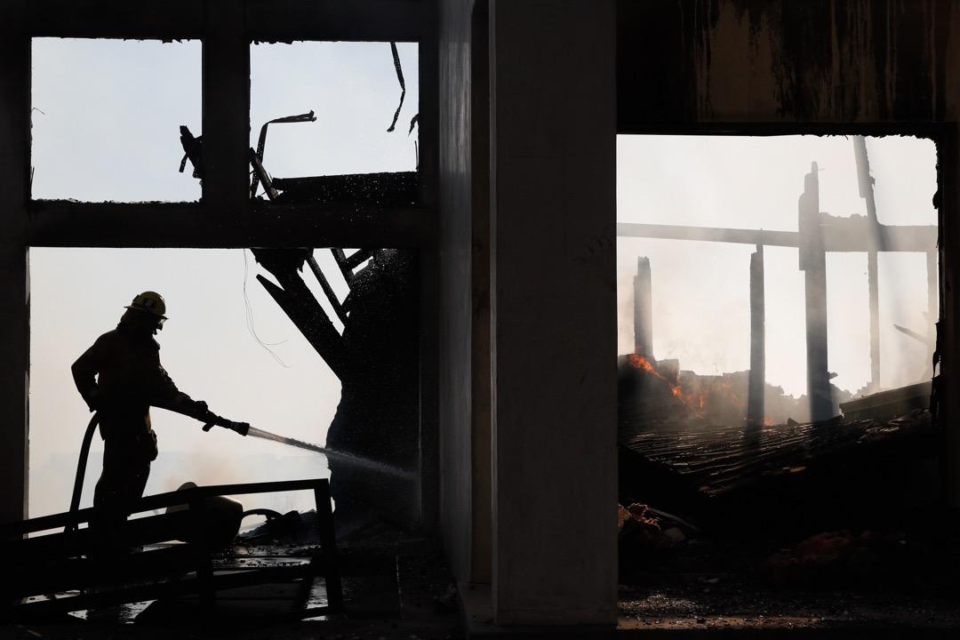 2017年12月6日,美國加州南部文圖拉郡爆發大型山火後,一名消防員在洛杉磯的貝萊爾區的一個災場清理現場。