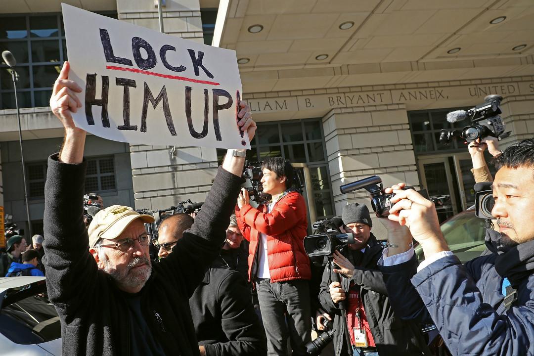2017年12月1日,美國前國家安全顧問弗林(Mike Flynn)在華盛頓參加法院聽證會。法院外示威者舉牌抗議。 攝:Chip Somodevilla/Getty Images