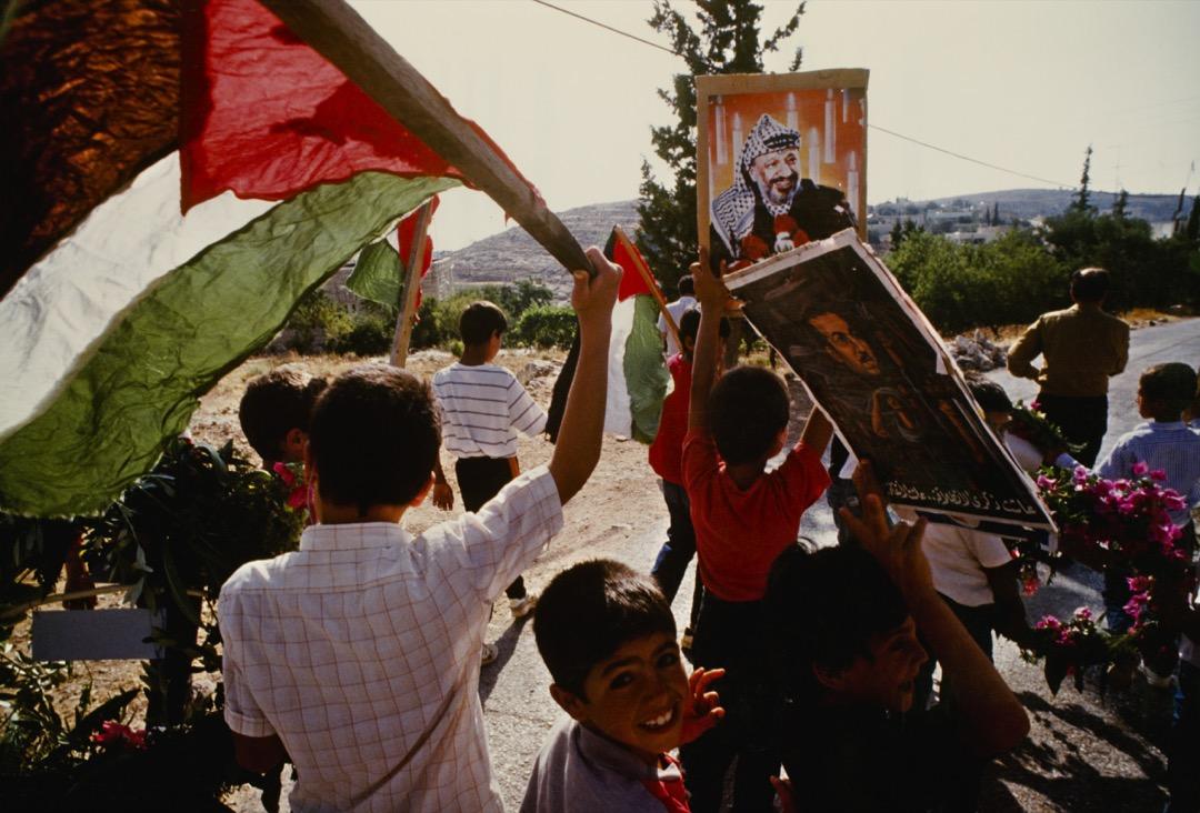 1989年6月,在巴勒斯坦被佔的土地上,巴勒斯坦兒童舉標語和旗幟表示支持巴解組織領導人阿拉法特。
