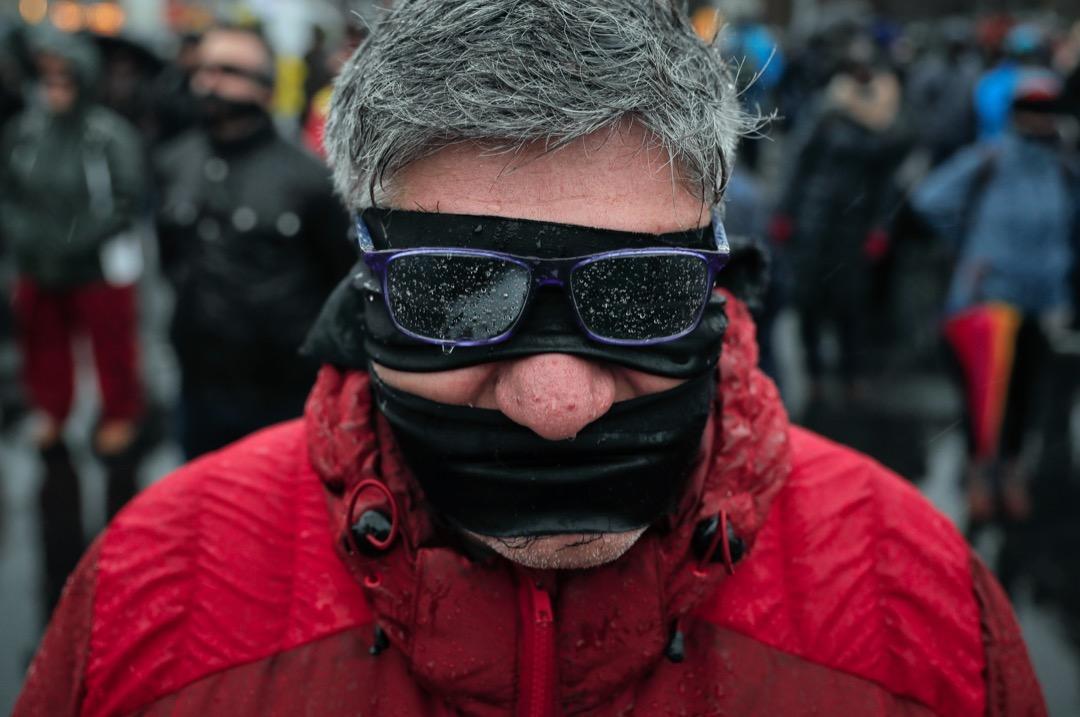 2017年12月17日,羅馬尼亞城市布加勒斯特,一名參與反對修改司法制度的示威者冒著低溫和雨水,在政府總部外用黑色緞帶遮住他們的嘴和眼睛,以示抗議。評論認為,修改司法制度會削弱對高層腐敗的懲罰。