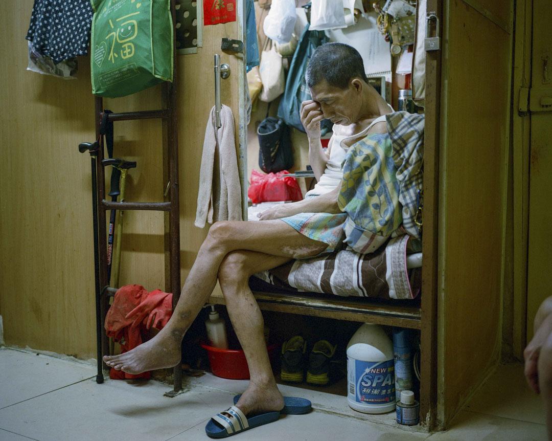 2017年6月,港島區一個板間房,住客坐在床邊看電視。