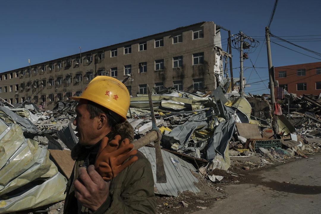 拆遷工人拿著鋤頭在廢墟中走過。