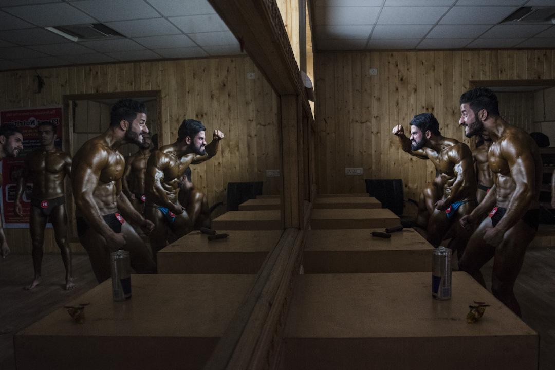2017年11月28日,印度,健美運動員在參加健美比賽之前,在後台對著鏡子演練。