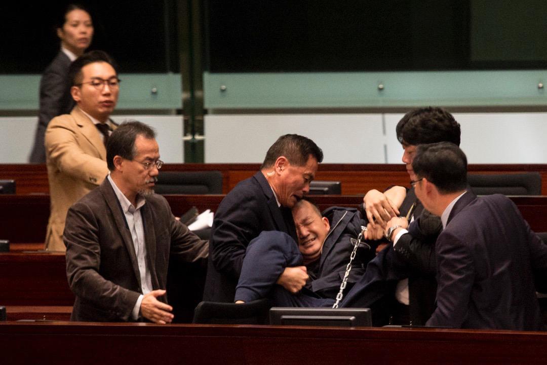 「人民力量」陳志全遭立法會主席梁君彥要求離開會議廳後,一度嘗試用鐵鏈將自己鎖在座位上,但被立法會保安制止並抬離會議廳。  攝:林振東 / 端傳媒