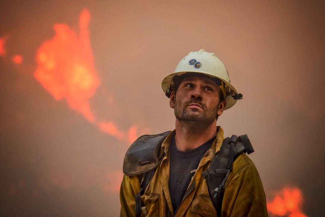 2017年12月11日,美國南加州山林大火已燒了超過10天,近20萬人被迫逃離家園之際,大火吞噬近800幢建築物,還有田地和森林,並至少導致一人死亡。圖為消防員Nikolas Abele正在山坡上觀察火勢。