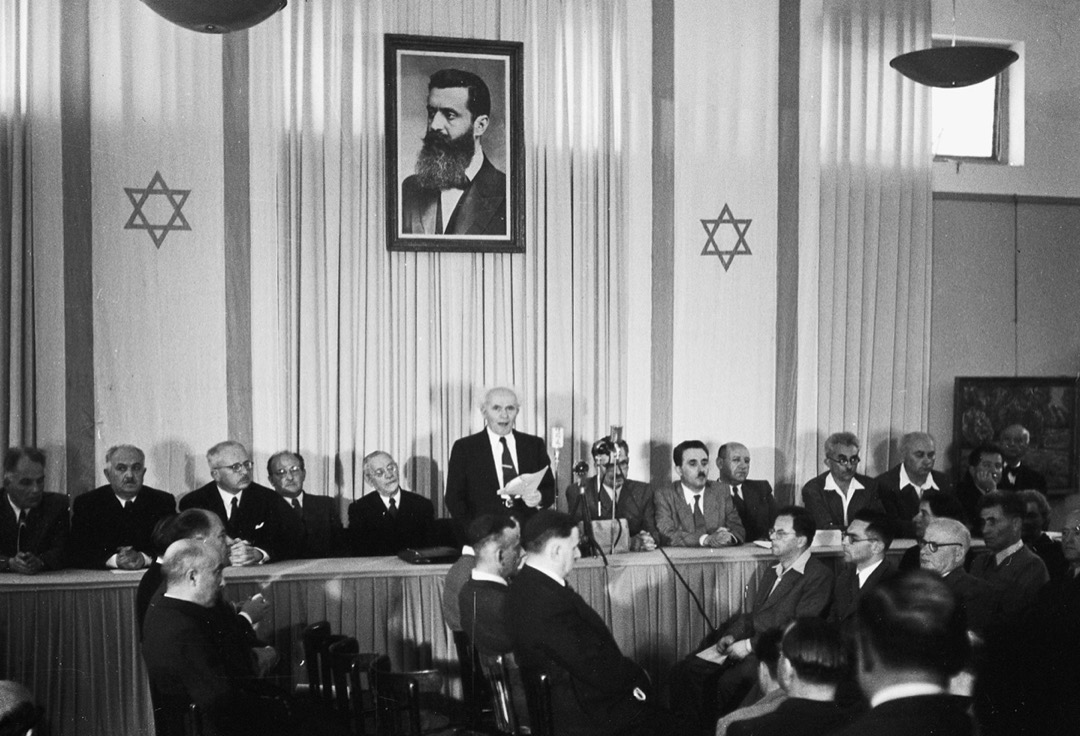 1947年11月29日,聯合國通過了181號決議的分治方案,將在巴勒斯坦地區分別建立兩個國家,猶太人居住的以色列和阿拉伯人居住的巴勒斯坦,而耶路撒冷因其地位特殊而由一個「國際特別政權」管理。圖為1948年5月14日,以色列第一任總理古裡安在特拉維夫宣讀以色列獨立宣言。